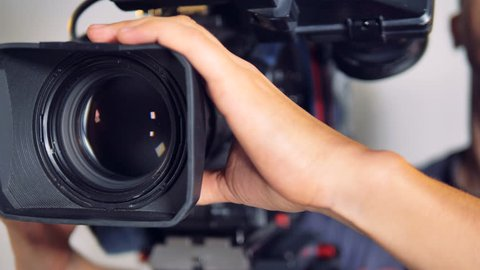 Male hands hold and move a large professional video camera in a close-up view.