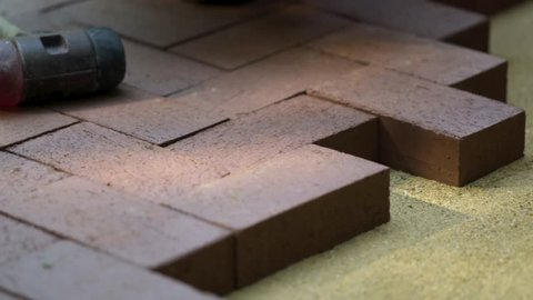 Closeup of a man setting brick pavers into place in a herringbone