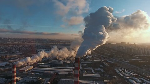 Pipes with smoke: industrial production, plant, air pollution. Dense thick smoke comes from industrial red-white pipes: from a bird's eye view. Industrial zone: smoke comes from the pipe.