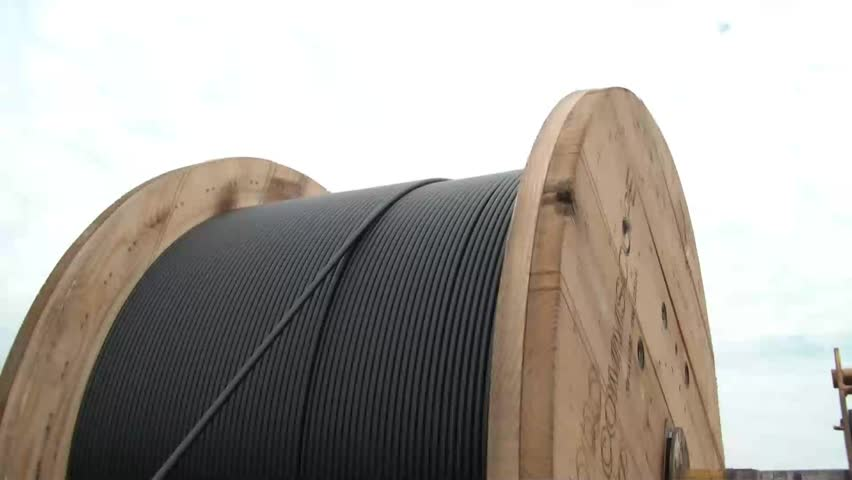 Clip of fiber optic cable being unreeled past workers and into actual pvc and hole underground.