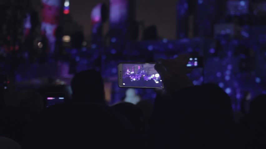 People taking video 3D mapping light show on a mobile phone. Hands of peoples taking photo to 3D mapping show on smartphone