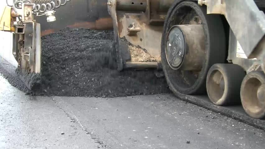 Clip of heavy equipment asphalt laying machine dropping blacktop tar onto new parking lot for school.