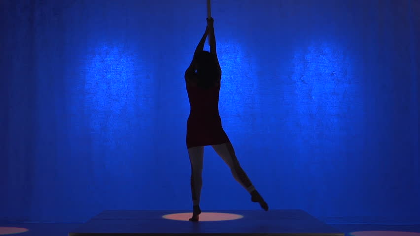 Aerial hoop performer, blue background, spinning silhouette