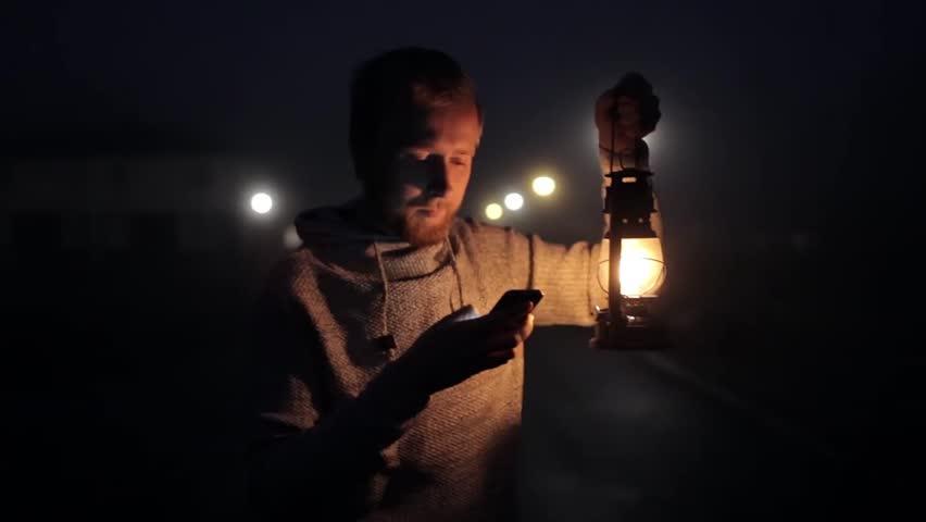 Man with phone and kerosene lantern on a foggy street | Shutterstock HD Video #32722195
