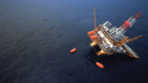 Oil Rig accident. Collapsed Oil Platform. Lifeboats waiting for rescue.