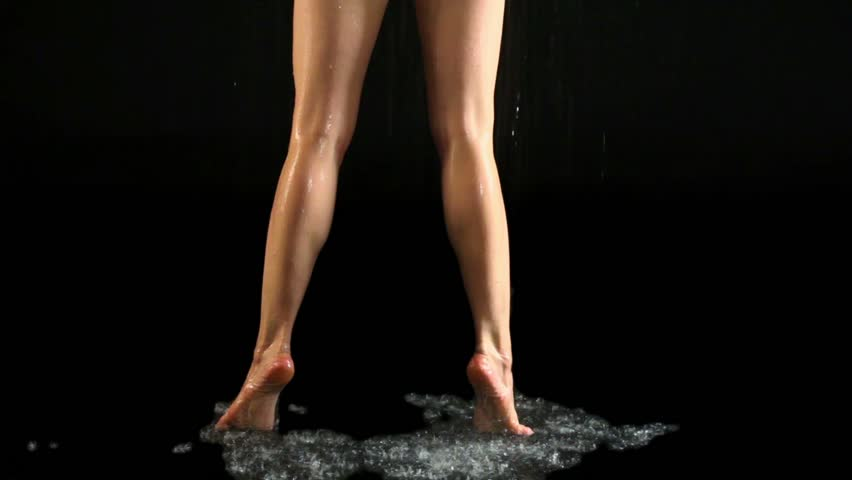 Girl stands on tiptoes under water in dark studio, only legs are visible