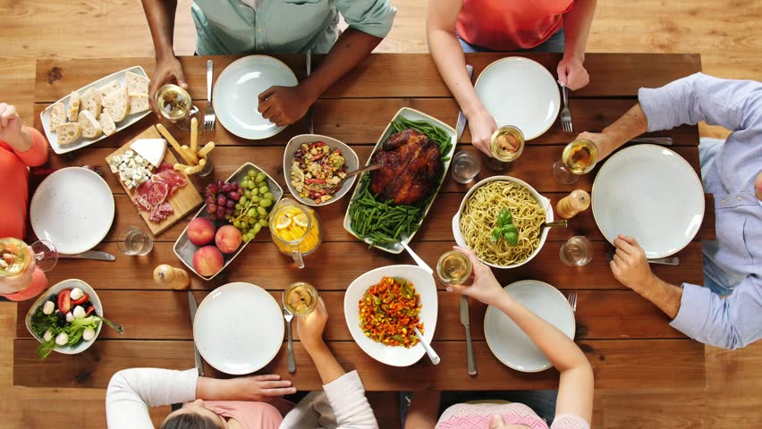eating and holidays concept - group of people at table with food clinking wine glasses #32760775