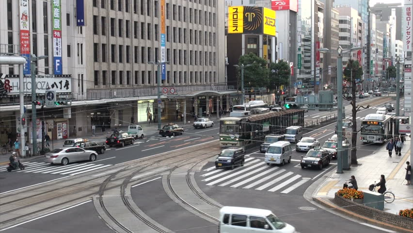 HIROSHIMA, JAPAN - 29 OCTOBER 2012: Busy intersection sees streetscars (trams) and regular traffic flow through during rush hour in Hiroshima, Japan
