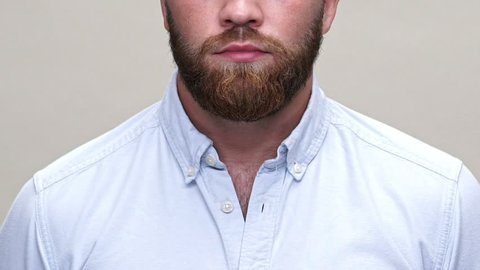 Cropped close up view of bearded man in shirt showing silence gesture over gray background