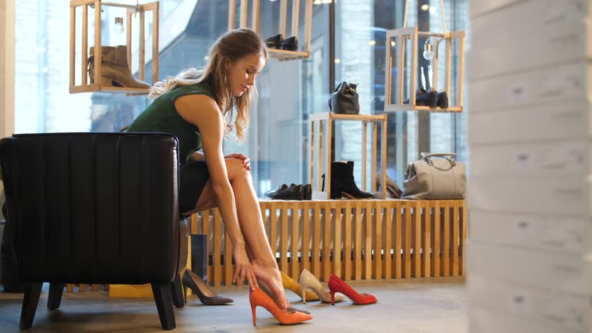 Sale, shopping, fashion and people concept - young woman choosing heeled shoes at store