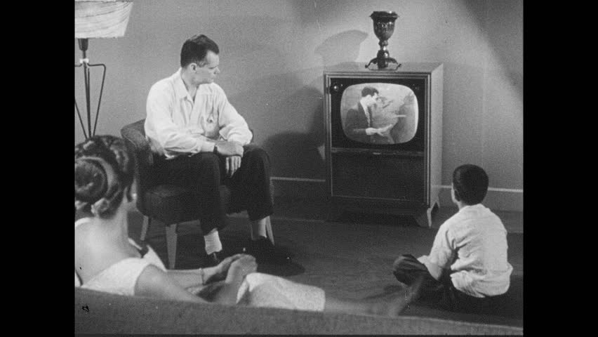 1950s: Family gathered around the TV set in a living room. Hurricane special bulletin plays on TV. Weather man announces hurricane.