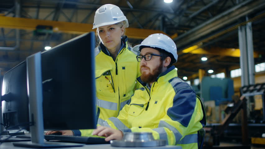 Male Industrial Engineer Works on the Personal Computer while Female Manager Talks about Project. They Work in Heavy Industry Manufacturing Factory. Shot on RED EPIC-W 8K Helium Cinema Camera. | Shutterstock HD Video #32793175