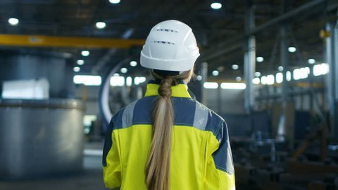 Following Shot of Female Industrial Worker in the Hard Hat Walking Through Heavy Industry Manufacturing Factory. In the Background Various Metalwork Project Parts Lying.  Shot on RED EPIC-W 8K Helium