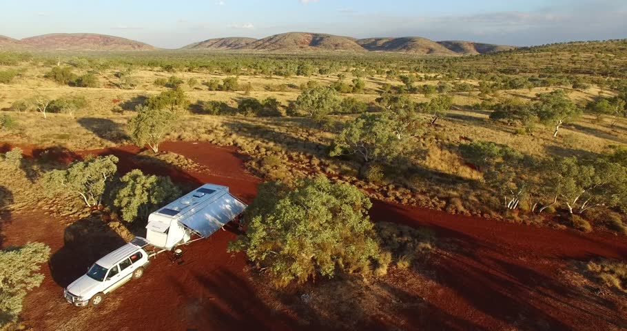 Early morning aerial views of four wheel drive vehicles, caravans and RV's free camping in the outback near Munjina Gorge in the Karijini National Park in Western Australia.