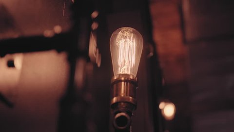 Male hand Switch electrical relay retro garland. Industrial light bulbs. Retro lighting in loft style. Lighting decor. Retro light bulb filament close up. Old vintage light bulb. Lamp in loft style.
