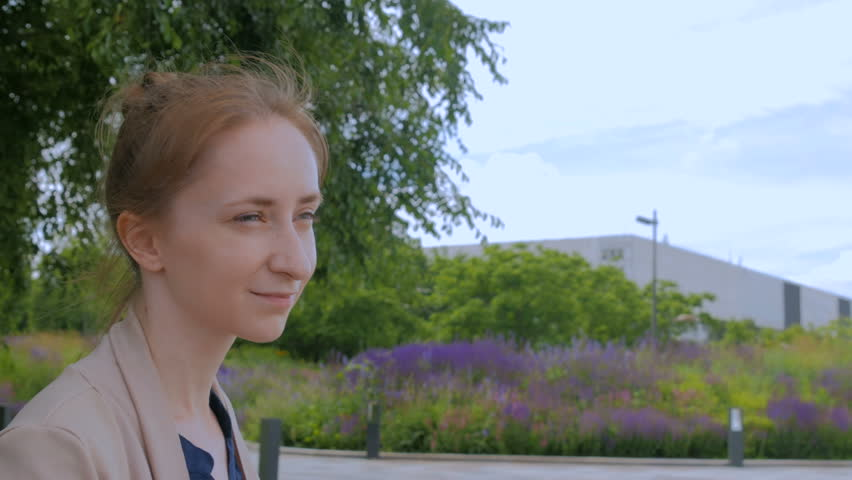 Portrait of young woman smiling and looking around in the Moscow park Muzeon