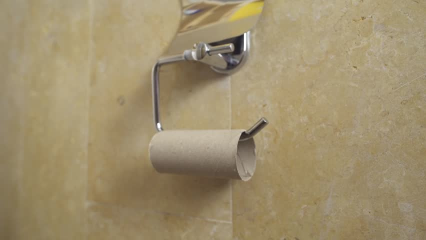 Hand reaches toilet paper and discovers there is no paper left