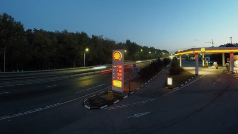 ROSTOV-ON-DON, RUSSIA - JUL 04, 2015: Transport traffic on highway near gas station of Shell company at morning during sunrise. Timelapse