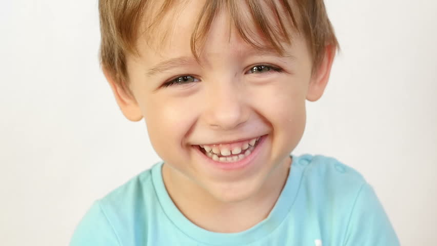 Close-up of a child looking and smiling at the camera in slow motion. The child shows joy and a big smile