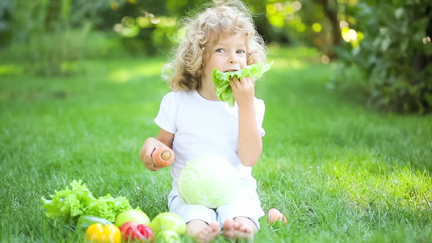 Happy child eating vegetables in spring park. Healthy eating concept