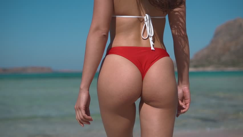 beautiful young girl buttocks walking to the sea