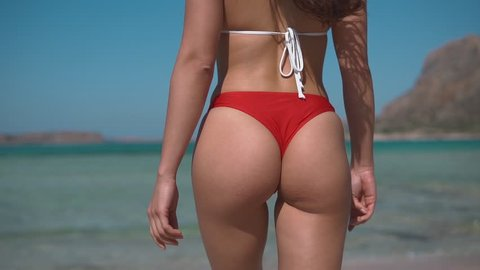 beautiful young girl buttocks walking to the sea