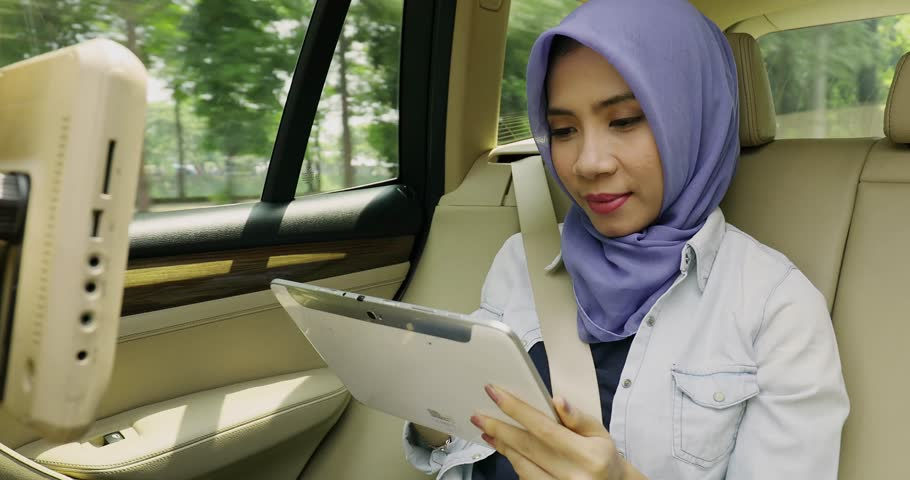 JAKARTA, Indonesia. November 15, 2017: Young muslim woman using a digital tablet while wearing a veil in the car, shot in 4k resolution