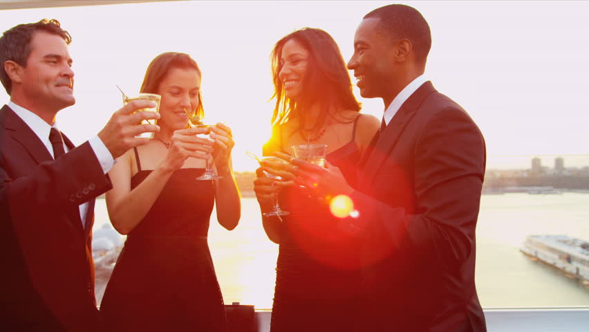Multi ethnic young attractive women and men laughing and drinking at cocktail roof party dressed in black shot on RED EPIC