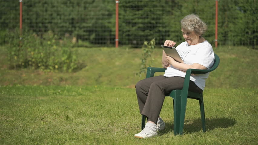 Mature old woman dressed t-shirt sitting on the background the green park  outdoors in summer holds a silver computer tablet for looking the images.