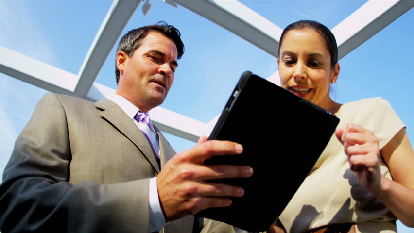 Team of confident Caucasian male and female managers using internet on tablet computer on rooftop