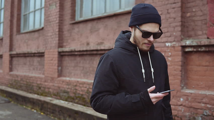 Handsome hipster young man in black jacket and sunglasses using mobile phone on the street slow motion | Shutterstock HD Video #32893195