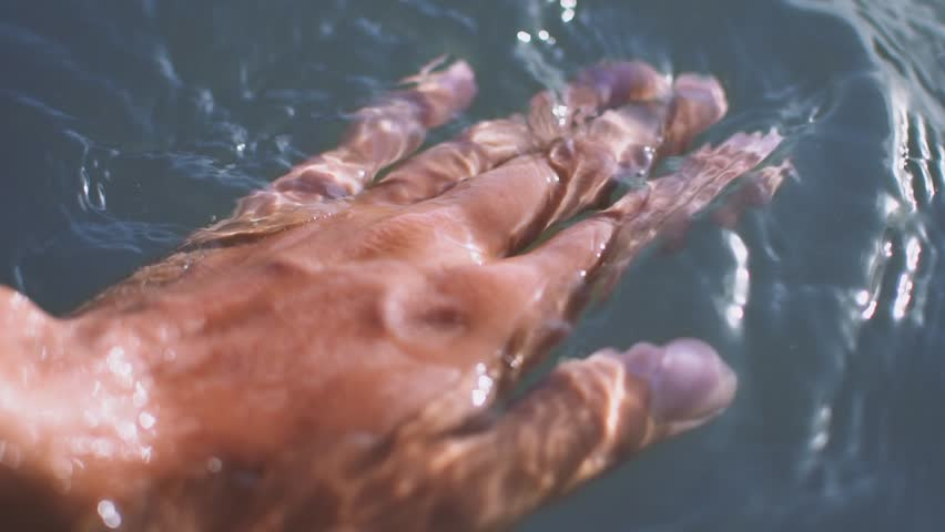 Unrecognizable young man caressing water with soft hands and sliding with fingers on its surface on sunny summer day. Enjoying and relaxing in infinity pool at luxury resort SLOW MOTION CLOSE UP  | Shutterstock HD Video #32906425