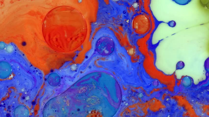 Colorful paint drops mixing in water. Ink swirling underwater. Liquid paint colorful bubbles patterns of moving surface,  river of liquid, movement of colorful paint.