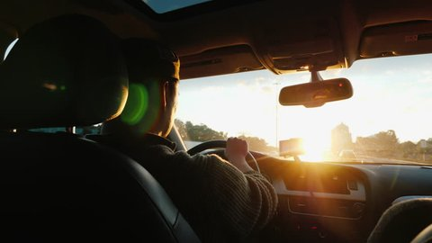 An Asian man drives a car along the highway, the setting sun shines in the windshield. Back view