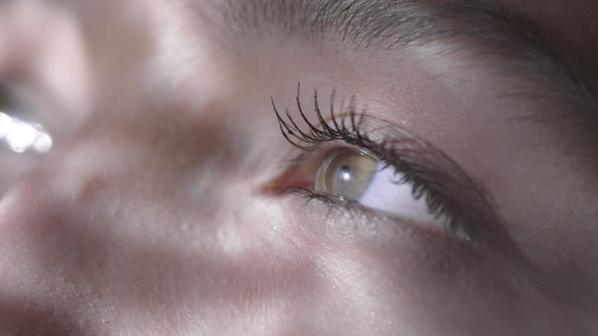 Close up of green eyes of unrecognizable woman looking up as soft light rippling on her face