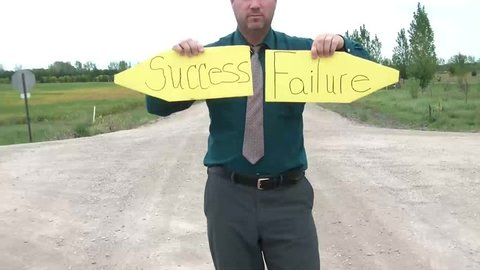 Businessman holds up pointed yellow signs at dirt road intersection reading success in one hand and failure in the other.