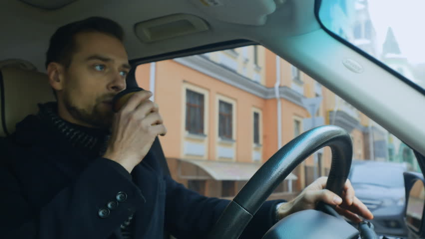 Businessman drinks coffee while drives the car