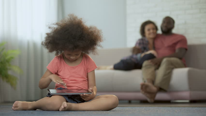 Young parents enjoying joint pastime watching their daughter playing on tablet