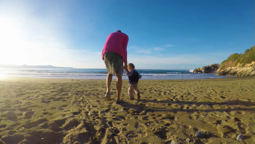 A mother and her son are playing on a beach
