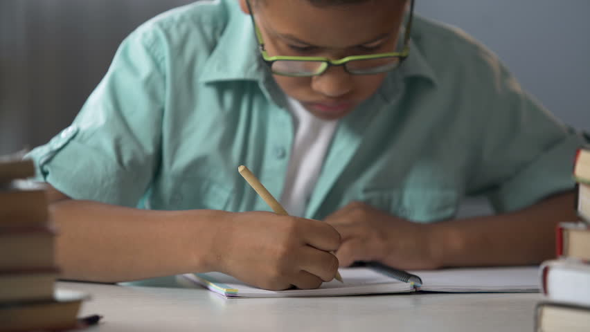 Elementary school pupil diligently writing letters in his notebook, calligraphy | Shutterstock HD Video #33018970