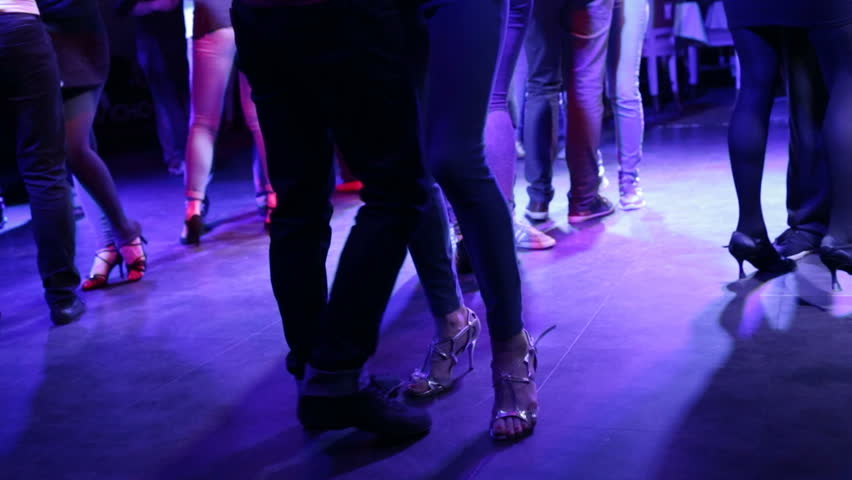 A young couple walks to the music at the disco. Night, indoors, party, disco lights on the dance floor a lot of people #33021085