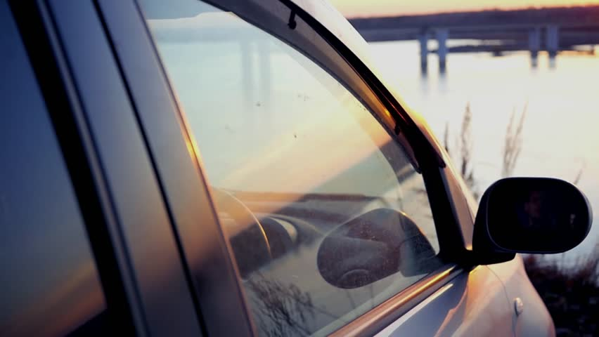 The man opens a window in the car and admires the beautiful sunset on the river at the bridge, sitting in the parking lot in the car. slow motion, 1920x1080, full hd