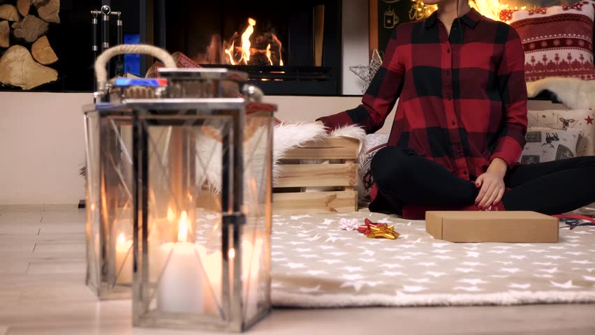 Woman wrapping a christmas gift at home