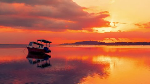 Timelapse Fishing boat on the Gili sea with a gorgeous red sunset as a backgound, Indonesia
