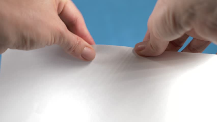 Hands tearing paper sheet, closeup on a turquoise background. 4k, slow motion   Shutterstock HD Video #33078997