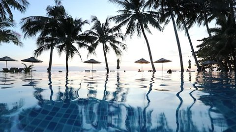 Swimming pool in beachfront tropical hotel resort with coconut palm trees landscape for beach holidays vacation, luxury destination