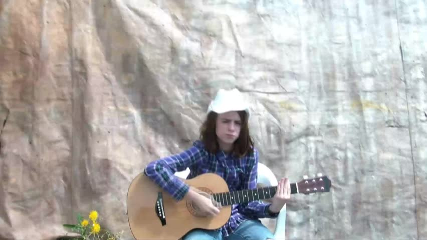 Cowgirl is playing guitar in sunlight with cowboy hat on while laughing and strumming emphatically, canvas as backdrop.