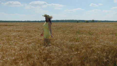 Woman in flower diadem and yellow dress walks on golden wheat field at sunny day