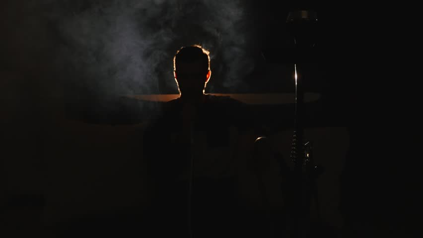 Young man smokes hookah and lets out smoke rings in a dark room close up