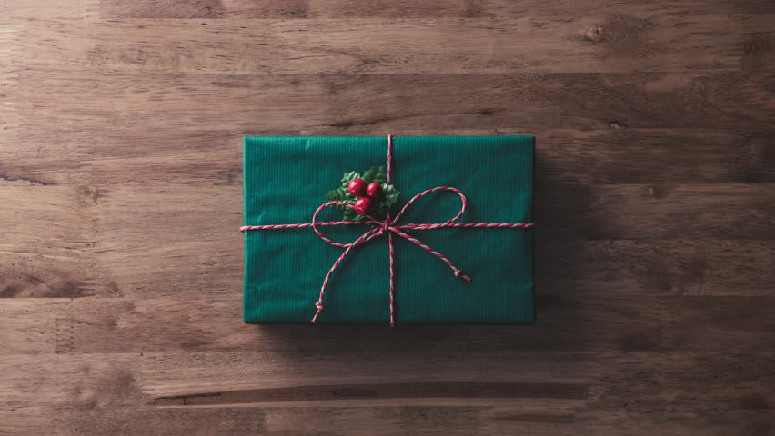 Colorful alternate Christmas and New Year holidays gift boxes on wood table with blank space at the end - top view, stop motion | Shutterstock HD Video #33102295